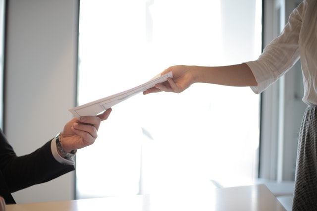 job applicant passing their document over