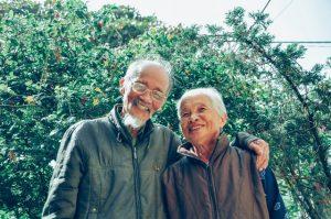 smiling elderly couple in garden
